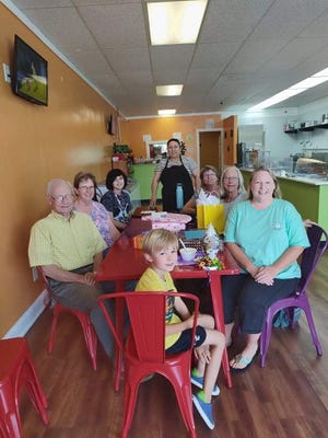Claudia Payan, standing, is pictured with Kathy Whitfield and her family, frequent visitors Delicias Las Reynas Mexican restaurant located on Trent Road in New Bern.