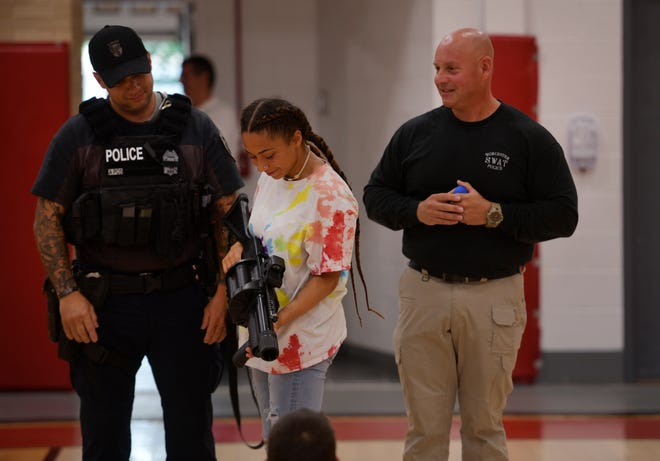With members of the Worcester Police Department standing beside her, Anna Maria College student Jordan Clarke holds a weapon as Sgt. Shawn Barbale, right, looks on.