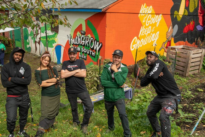 Khalil Guzman, Ivy Orth, Travis Duda, Ryan Gardell and Grhimm Xavier pose near a mural that is being painted at the Youth Grow Garden earlier this month. POW! WOW! Worcester kicked off Aug. 13 and runs through Aug. 22.