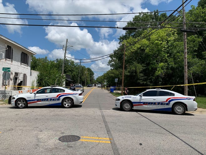 Fayetteville police vehicles block the entrance to the 300 block of South Cool Spring Street where a man was shot and killed Thursday morning.