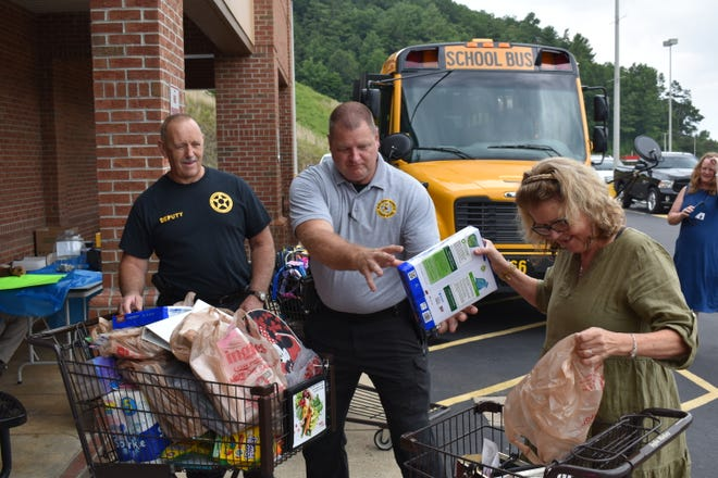 From left, Madison County Sheriff's Office Deputy Russell Shepherd and Sgt. Daniel Porche collect school supply donations from a local resident Aug. 4.