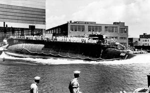 In this July 9, 1960 file photo the 278-foot long nuclear-powered attack submarine USS Thresher, a first in its class boat, is launched bow-first at the Portsmouth Navy Yard in Kittery, Maine.