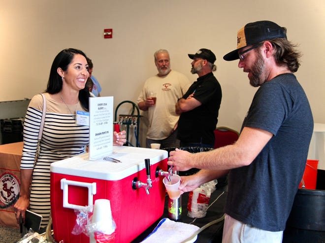 Chris Ayers of Intracoastal Brewing Company in Eau Gallie, right, serves a beer to Samantha Selig at the recent Economic Development Commission board meeting and investor update in Cocoa Village.