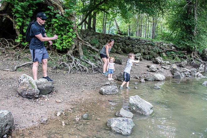 (L-R) Brian and his family Mandy, Makenna, and Mason throw rocks into a stream at the Paint Creek Dam site on August 5, 2021, outside of Bainbridge, Ohio.