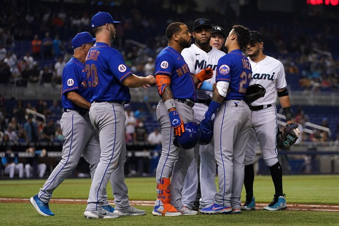 New York Mets left fielder Dominic Smith (2) restrains shortstop Javier Baez (23) in the 8th inning after on field altercation against the Miami Marlins at loanDepot park in Miami on Aug. 3.