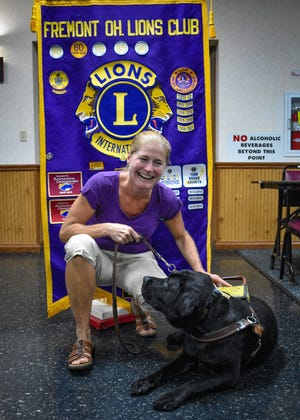 Tris looks nonchalantly at Meredith Cook as Cook responds with laughter to Tris' desire to lay down during their visit to the Aug. 3 Lions Club meeting.