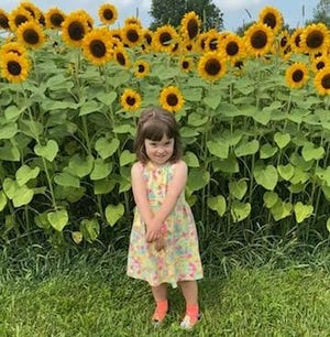 Maddie Zajac stands in front of a sunflower field.