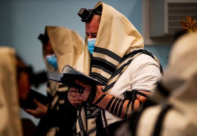 Observant Jews wore masks along with their Tefillin (black boxes) and Tallit (prayer shawls) during a recent morning prayer service at Chabad of Kentucky.
