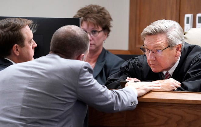 District Attorney Ray Crouch and Defense Attorney Luke Evans talk with Judge David Wolfe during the trial of  Steven Wiggins who is charged with first-degree premeditated murder and first-degree felony murder in the shooting death of Sgt. Daniel Baker.