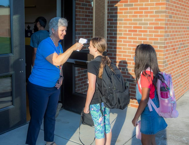 Tina Muckle takes students' temperatures as they enter the building during Stoner Creek Elementary School's first day which took place in one of the wings at West Wilson Middle School due to the 2020 tornado Thursday, August 5, 2021.
