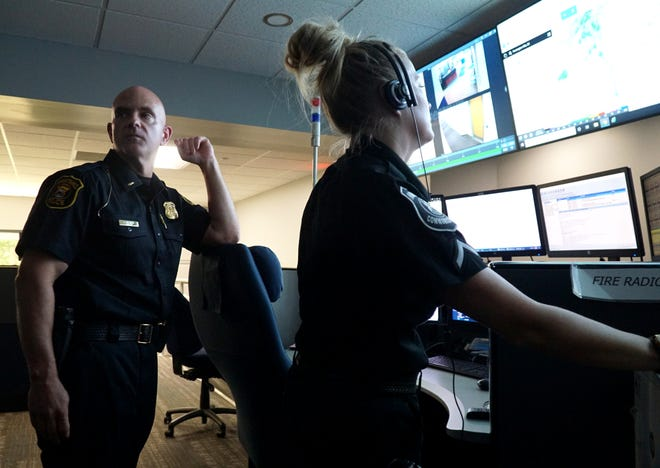 Farmington Hills Police Officer Mike Conolly and communications specialist Angie Konwinski in the department's dispatch center.