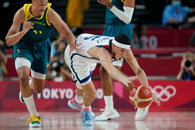 United States's Devin Booker (15), right, steals the ball from Australia's Dante Exum (11) during men's basketball semifinal game at the 2020 Summer Olympics, Thursday, Aug. 5, 2021, in Saitama, Japan. (AP Photo/Charlie Neibergall).