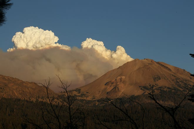 Clouds of smoke from the Dixie Fire rise behind Lassen Peak on Wednesday evening, Aug. 4, 2021.