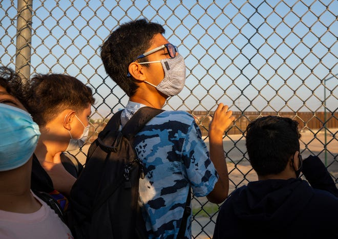A student tries to look at the front of the line as students await to enter the U.S. from Ciudad Juarez at the Zaragoza Bridge. Hundreds of students cross the international border between Ciudad Juarez and El Paso on a daily basis to attend schools.