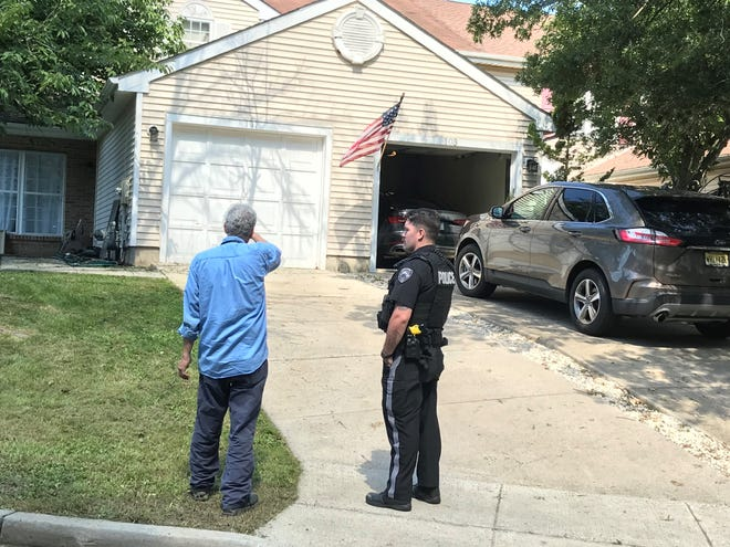 A Westampton Police officer talks with an unidentified man outside the residence of Rhys Lershe, who was arrested Aug. 4, 2021 after reportedly assaulting his elderly neighbors and taking their vehicle.