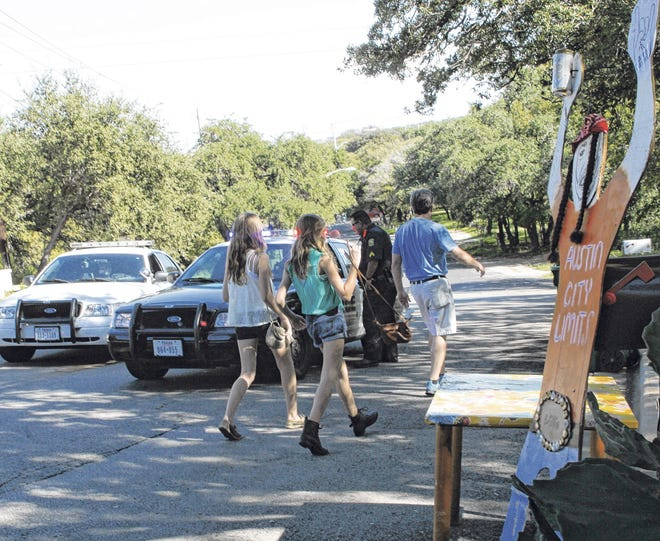 A Rollingwood police officer mans a drop-off point near the east end of Rollingwood Drive in 2012, where thousands of people passed through the small city en route to Austin City Limits Festival. The city is working with Austin officials to minimize the traffic snarls this year.