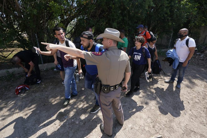 In this June 16 file photo, a Texas Department of Public Safety officer in Del Rio directs a group of migrants who crossed the border and turned themselves in.