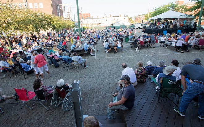 Hundreds of visitors to Downtown Alliance watch a performance of Jimmy & the Soul Blazers, upper right, on Thursday, Aug. 5, 2021, near the downtown caboose during the opening night of the Greater Alliance Carnation Festival Rib & Food Fest on East Main Street.
