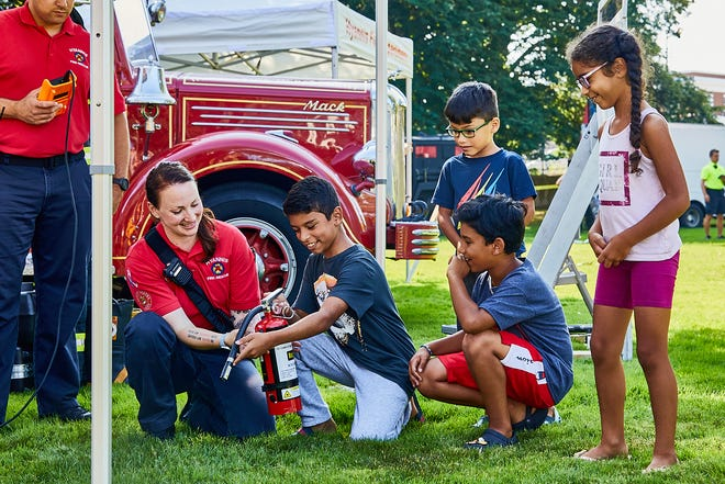 People of Action, the Barnstable Police Department, and the Town of Barnstable hosted the 5th Annual Barnstable Unity Day Celebration on the Hyannis Village Green on Friday. Rebecca Tatzel, from the Hyannis Fire Department, educates 10-year-old Abner Nascimento, along with 5-year-old Joao Monteiro, 8-year-old Jean DaSilva, and Rebecca Nascimento about fire safety and how to properly use a fire extinguisher.