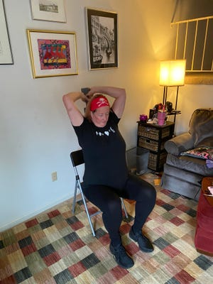 Kerrie Bloss works out her triceps during her half-hour exercise routine. Bloss has lost 150 pounds since the start of the pandemic with exercise and mindful eating, she said.