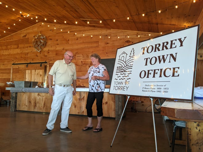 Retiring Supervisor Patrick Flynn was surprised with the new sign for the Town Offices which are now dedicated to his service at that of his father before him.