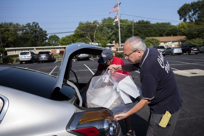 Families across Ohio faced hardships during 2020, but a new report on the State of Poverty in Ohio puts numbers behind those experiences. In this Aug. 4 file photo, volunteer Gene Bassin loads bags of clothing into a customer's car during a clothing distribution for those in need.