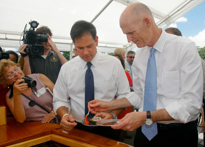 As media documents them, U.S. Sen. Marco Rubio gets a dollop of cocktail sauce to go with his oyster from Florida Gov. Rick Scott Tuesday, Aug. 13, 2013, in Apalachicola, Fla. Scott announced that the state of Florida will be suing Georgia, alleging that their increased consumption of water has limited freshwater flows into the Apalachicola River. Florida's oyster industry has seen a near collapse in the last two years because of reduced water flow and because of drought. Yesterday, the federal government declared a fishery disaster for those who harvest oysters out of the Gulf of Mexico. (AP Photo/Phil Sears)