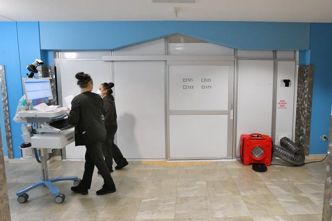 Health care workers make their way past a sealed-off suite at Wolfson Children's Hospital where pediatric COVID-19 patients who are not in the intensive care unit are treated.