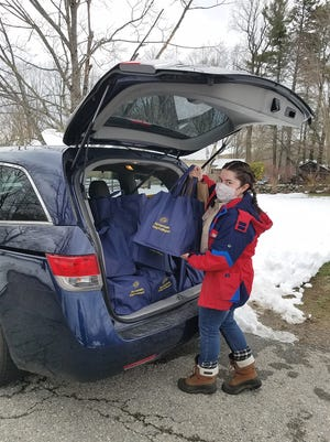 """Abby Bennett of Phillipston is shown loading a car for her """"Spread Joy, Not Germs"""" Eagle Scout project."""