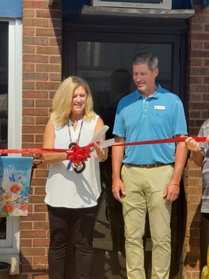 Donna and Jeff Merideth are shown at the recent ribbon cutting held to officially open their new business, RidgeWood Pharmacy at 103 North Prospect in downtown Cambridge.