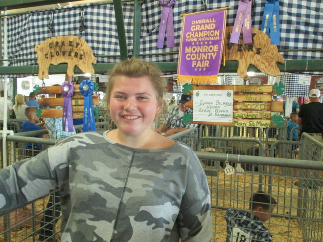 Cyanna Baumann, 18, of Monroe stands by her pen in the hog barn after being named best showman of 4-H pigs at the fair.