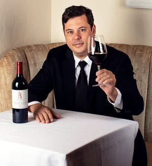 Cafe Boulud sommelier Imre Papp with a glass of wine.