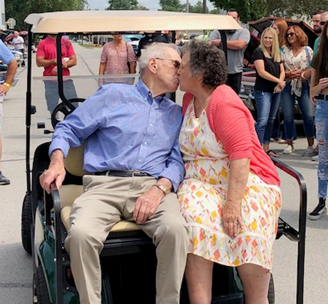 Lloyd and Carol Aberle share a romantic moment on the back of their new golf cart in downtown Fairbury for their 66th wedding anniversary.