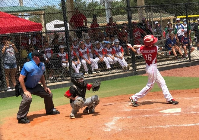 Trey Longuil holds on to the ball as teammate Ben Cheek strikes out the final batter of the game in Dover's 8-2 win over Key West, Florida in the opening game of the Cal Ripken 10-year-old World Series Friday in Palm Beach Gardens, Florida.