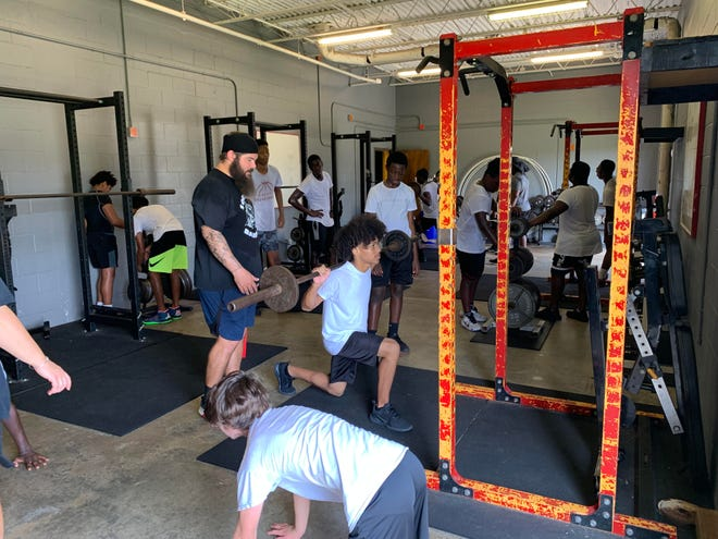 Santaluces assistant football coach Kyle Smith, standing, helps the players during a weight-lifting session this summer.