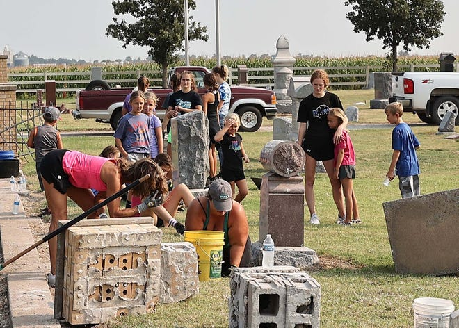 Volunteers from the community of St. John gather at Fairview Park Cemetery on Friday morning to clean up the aftermath of a semi-truck and trailer that crashed into more than 10 headstones  after breaking through brick pilars and gates on Thursday.