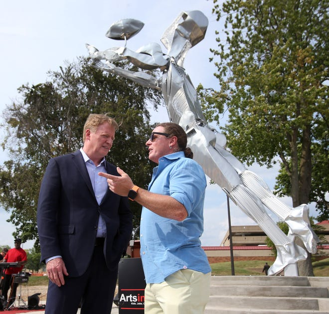 """NFL Commissioner Roger Goodell, left, speaks with artist Jack Howard-Potter after Friday's unveiling of the """"1958 Championship Game"""" sculpture in Canton."""