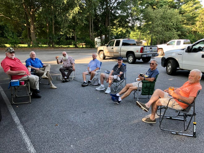 The Retired Old Men Eating Out group at Elizabeth Baptist Church carries out their weekly tradition in the church parking lot.