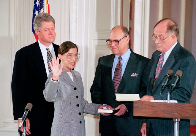 In this Aug. 10, 1993, photo, Supreme Court Justice Ruth Bader Ginsburg takes the court oath from Chief Justice William Rehnquist, right, during a ceremony in the East Room of the White House. Ginsburg's husband, Martin, holds the Bible and President Bill Clinton watches at left.