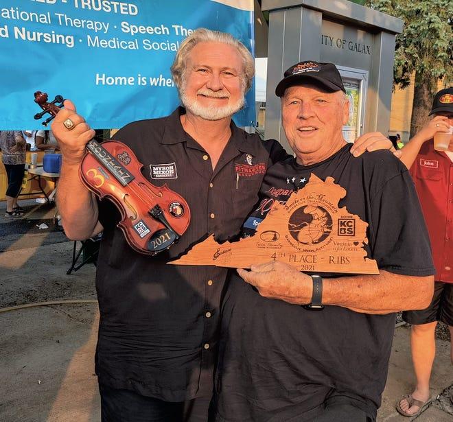 Alan Nichols and Myron Nixon pose at a barbecue judging event