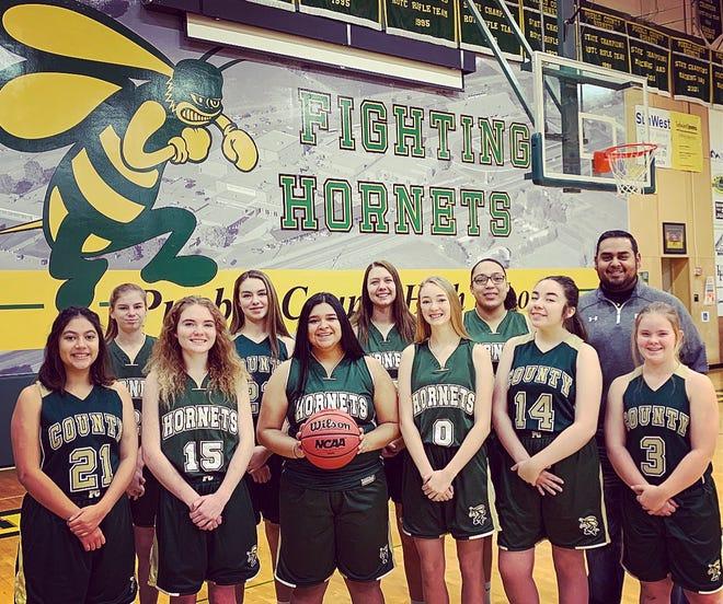 Jordan Martinez and his Pueblo County High School  freshmen girls basketball team pose for a team photo