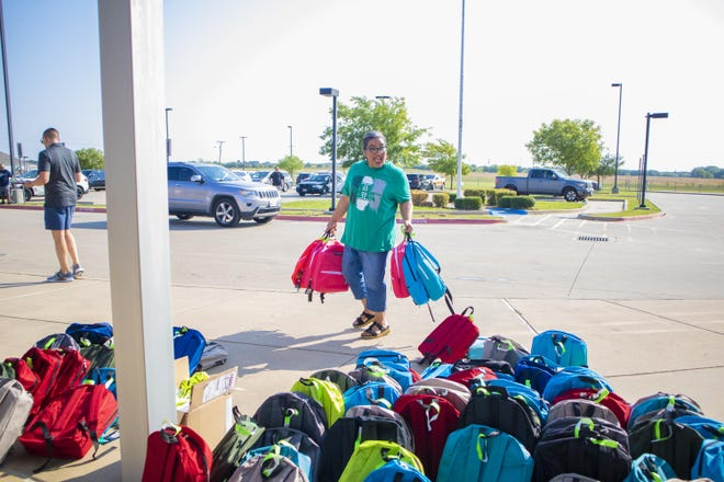 Volunteer workers set out backpacks for pickup at Clift Elementary on Saturday for Waxahachie ISD's Operation First Day of School. More than 1,000 backpacks with school supplies were donated to local families.