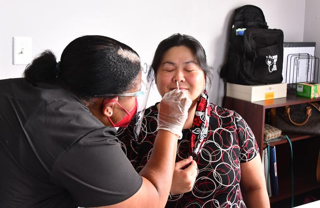 Cindy Yee of Titusville gets a COVID test from a nurse recently. COVID-19 tests like this one are randomly selected by the Centers for Disease Control and Prevention for genomic sequencing to determine which strain of the novel coronavirus is causing infections.