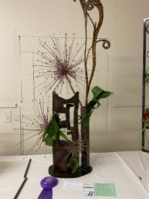 """Judy Widman's abstract design to interpret """"The Flame"""" by Jackson Pollock used allium, aspidistra and fascinated willow. Her card read """"movement, POW! Curly Cues! The unexpected ... Fireworks!"""""""