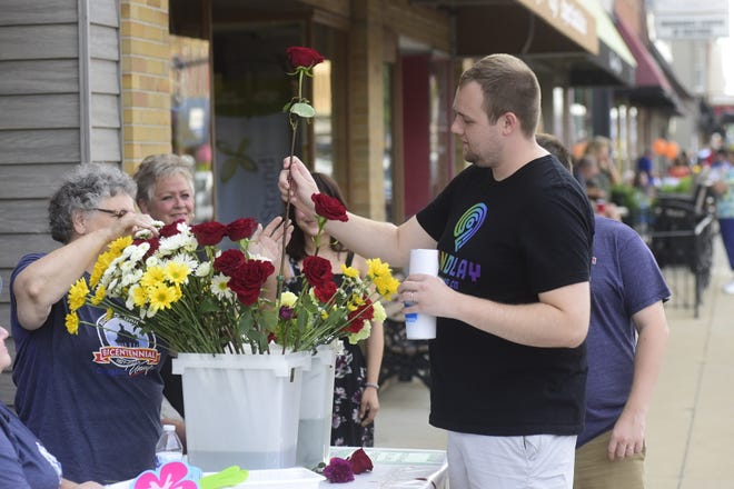 Jace Swingle gets a free flower from Debbie Bennett of Norton's Flowers during the August iteration of First Friday downtown Bucyrus.