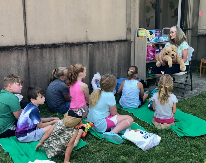 Deborah Crowdy speaks to children during a recent outdoor youth program at the Coshocton Public Library. Crowdy is retiring from the library as youth services manager, a position she had since 2018.