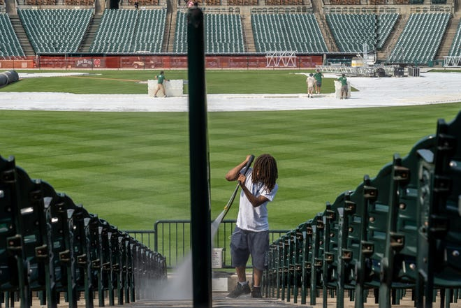 """Jonathan Washington of Detroit power washes seats in the outfield as crews work to clean and set up the field at Comerica Park in Detroit on Friday, August 6, 2021 to stage the open-air rock stadium before this Sunday's Guns N' Roses concert and next Tuesday's """"Hella Mega Tour"""" with Green Day, Fall Out Boy and Weezer."""