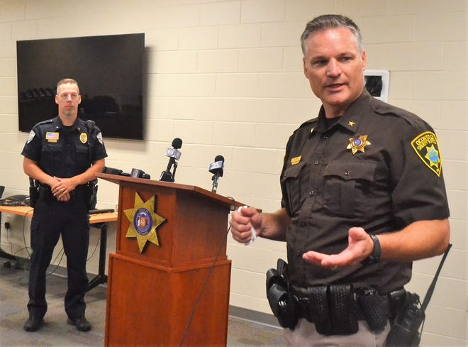 Oconto County Sheriff Todd Skarban, right, tells reporters during a news conference Aug. 6 that an Oconto Falls officer was in stable condition after she was shot while responding to 911 calls from a local residence. Oconto Falls Police Chief Brad Olsen is at left.