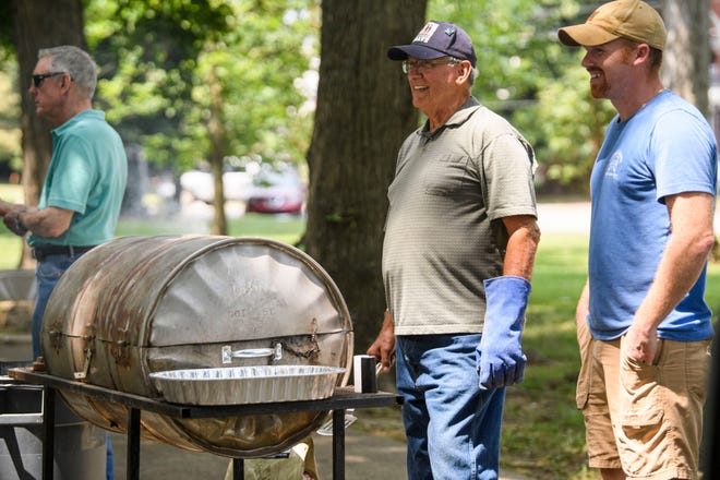 Dwight Crooks, center, runs a grill with burgers as he talks with John Musarra II, right, as they make free food to give out to first responders at the Central Park Gazebo in Downtown Henderson, Ky., from 11 a.m. to 2 p.m. Friday, Aug. 6, 2021. The lunchtime appreciation event was organized by the Henderson County Kentucky Republican Party, of which Crooks and Musarra are both members.