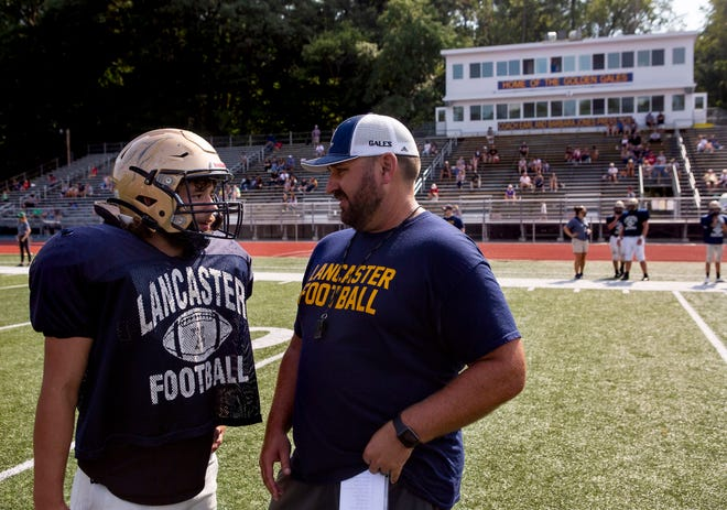 First-year Lancaster head coach Bryan Schoonover talks with senior Ty Hedges during the Golden Gales' scrimmage against Westerville North.